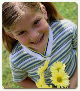 child with braces and flowers